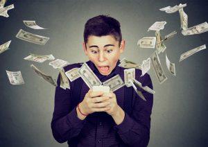 Erstaunter junger Mann mit Smartphone in der Hand inmitten von umherfliegenden Dollarscheinen
